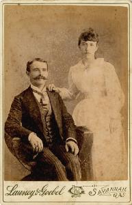 Portrait -- Man seated with standing woman.