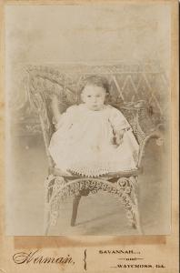 Portrait -- Infant seated in a wicker chair.